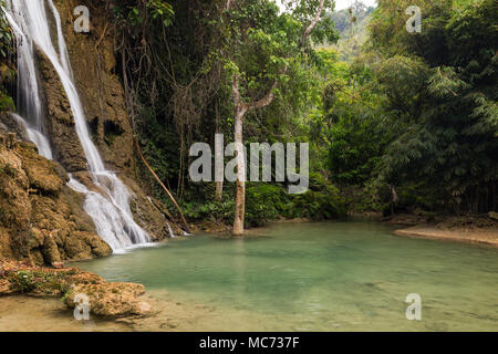 View of idyllic Khoun Moung Keo Waterfall, pond and lush trees near Luang Prabang in Laos. - Stock Photo