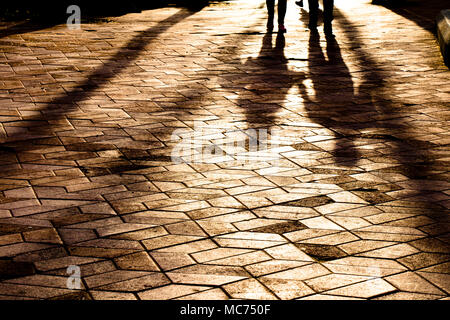 Blurry long shadows silhouettes of a couple walking on city patterned square in sunset - Stock Photo