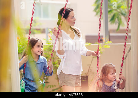 Mother with two daughters on playground, beautiful young mom rocks her precious girls on the swing, happy family spending weekend together - Stock Photo