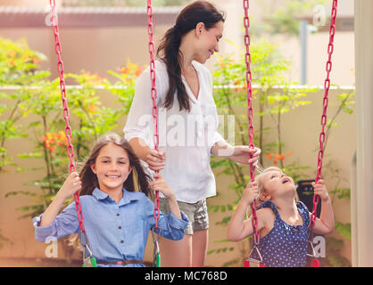 Mother with two daughters on a playground, beautiful young mom rocks her precious girls on the swing, amusement for outdoors kids, happy family spendi - Stock Photo