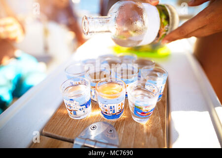 Party on the beach, refill glass with alcoholic beverage, drinking shots with friends, enjoying freedom, happy carefree summer vacation - Stock Photo