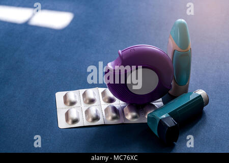 Set of asthma inhaler, accuhaler and anti-allergy pills for treatment asthma. Asthma controller, reliever equipment on dark blue background. Bronchodi - Stock Photo