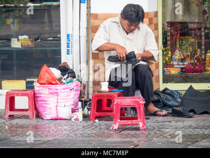 A man sitting on a plastic stool repairing shoes, working on the pavement on a street in Ho Chi Minh City, Vietnam. - Stock Photo