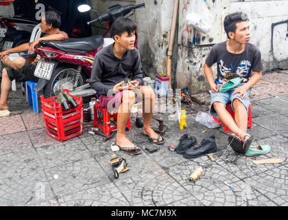 Two men sitting on plastic stools repairing shoes, working on the pavement on a street in Ho Chi Minh City, Vietnam. - Stock Photo
