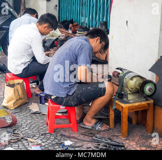 Three men sitting on plastic stools repairing shoes, working on the pavement on a street in Ho Chi Minh City, Vietnam. - Stock Photo