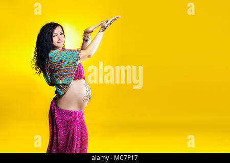 Pregnant happy woman in Indian sari with mehendi tattoo painted with henna on belly, fun fooling around on a yellow background. - Stock Photo