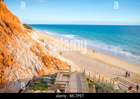 People relaxing on Falesia Beach with beautiful cliffs by Atlantic Ocean, Albufeira, Algarve, Portugal - Stock Photo