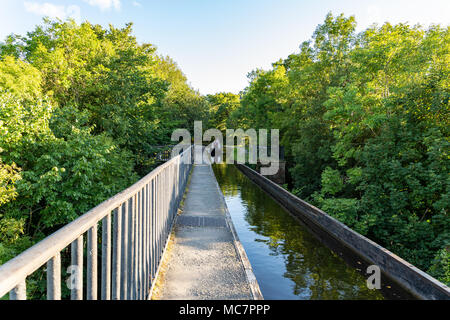 Near Froncysyllte, Wrexham, Wales, UK - August 30, 2016: People stering a Narrowboat over the Llangollen Canal, approaching the Pontcysyllte Aqueduct  - Stock Photo