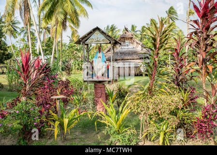 A Christian niche with a Virgin Mary statue in front of a Haus Tambaran, Korogo Village, Middle Sepik, Papua New Guinea - Stock Photo