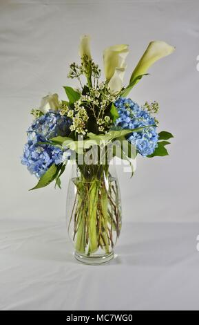 Beautiful tall glass vase filled with pretty flowers and fresh green leaves - Stock Photo