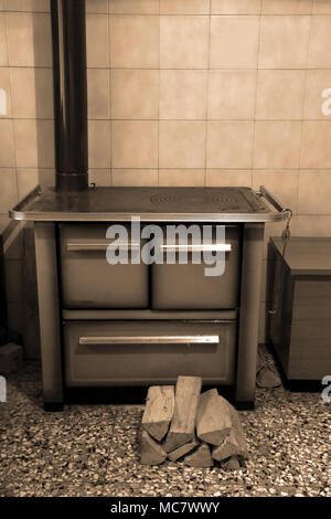 wood-burning stove in the kitchen of a chalet and the logs of wood on the floor with sepia toned - Stock Photo