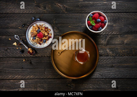 Fresh granola, muesli with yogurt, blueberries, raspberries, dried apple and cranberries with chia seeds. Fresh mixed berry fruit and maple syrup. - Stock Photo