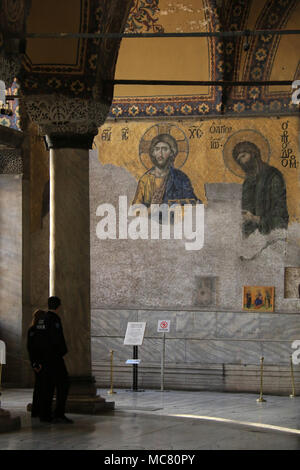 Tourists in front of parts of the Deësis mosaic, ancient Christian art showing Christ and John the Baptist, on the upper gallery inside Hagia Sophia - Stock Photo