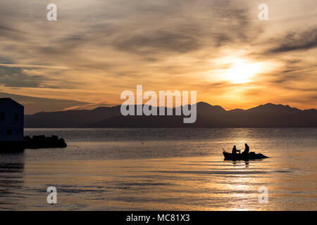 Silhouettes of two men rowing in a small fishing boat at a colorful golden cloudy sunrise in Corfu, Greece. Horizontal image - Stock Photo
