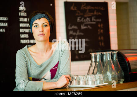 Waitress smiling in cafe, portrait - Stock Photo