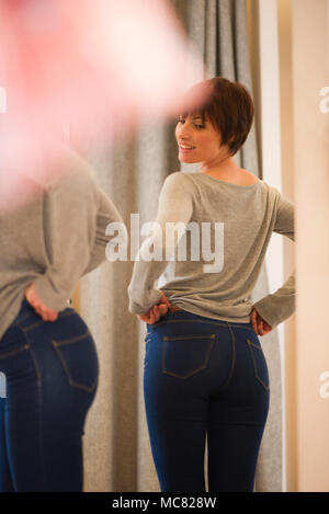 Woman trying on jeans in fitting room - Stock Photo