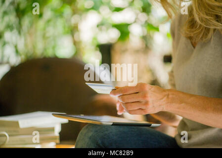 Woman using digital tablet and credit card, cropped - Stock Photo