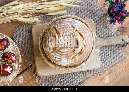 A loaf of sourdough bread in a basket on a wooden table - Stock Photo
