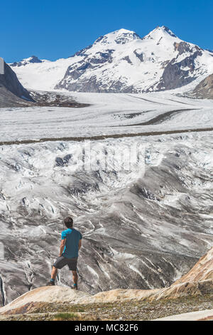 Lone male climber looking out, Aletsch Glacier, Canton Wallis, Switzerland - Stock Photo