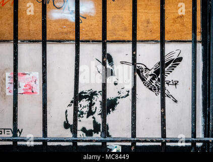 Street art featuring a rabbit and humming bird behind bars in a narrow alley in the centre of Bristol UK - Stock Photo
