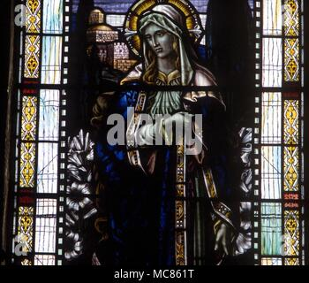 CHRISTIAN Mary, mother of Jesus, with her floral attributes of the Lily. Stained glass window (19th century) in the church of Newchurch-in-Pendle - Stock Photo