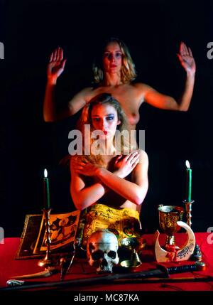 Sky-clad members of a wiccan group standing in front of a specially constructed pagan altar. - Stock Photo