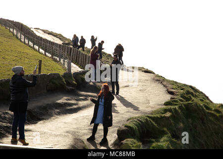 Young couples take photos of themselves on the Cliffs of Moher, County Clare, Ireland - Stock Photo