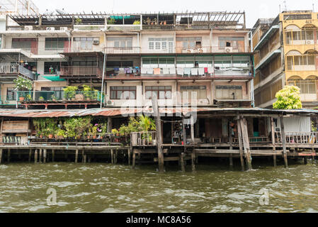 Rickety old buildings made from corrugated iron and wood alongside the Chao Phraya River in Bangkok, Thailand - Stock Photo