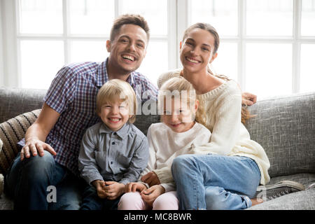 Portrait of happy multinational family with adopted kids laughing bonding together, smiling young couple embracing boy son and daughter girl sitting o - Stock Photo