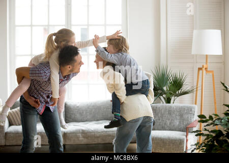 Happy young parents piggybacking son and daughter at home, smiling father and mother holding little kids on back spending time together, family having - Stock Photo