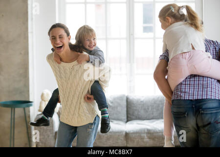 Happy mother laughing piggybacking little son playing with family at home, cheerful parents carrying kids on back having fun together, children boy an - Stock Photo