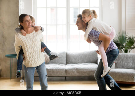 Laughing parents holding kids on back giving children piggyback ride playing together at home, cheerful family enjoying active funny game together, si - Stock Photo