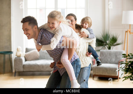 Happy loving dad piggybacking little daughter playing with family at home, smiling parents carrying kids on back, children boy and girl having fun tog - Stock Photo