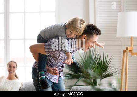 Happy dad holding little cute kid boy on back giving child piggyback ride having fun together at home, cheerful father playing with excited preschool  - Stock Photo