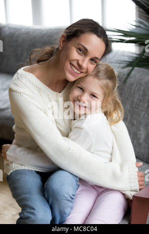 Happy single mother embracing cute little adopted girl looking at camera, smiling cheerful mom hugging preschool daughter at home, young diverse mommy - Stock Photo