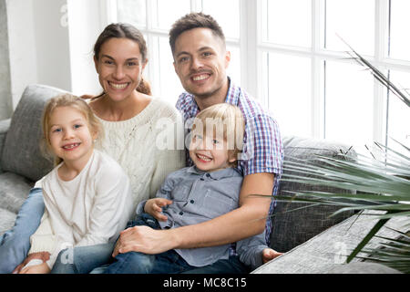 Portrait of happy multi-ethnic family embracing adopted kids siblings bonding together, young smiling adoptive parents hugging boy son and daughter gi - Stock Photo