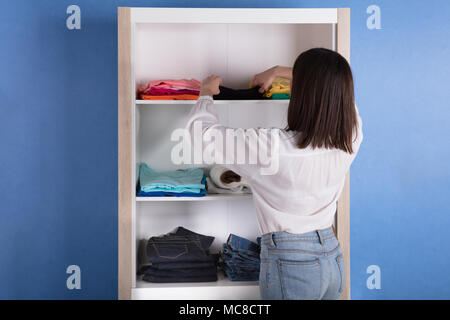 Rear View Of A Young Woman Choosing Cloth From Shelf - Stock Photo