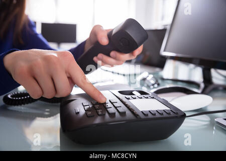 Close-up Of A Businessperson's Hand Dialing Telephone Number To Make Phone Call - Stock Photo