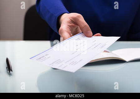 Close-up Of A Businessperson's Hand Giving Cheque Stock Photo