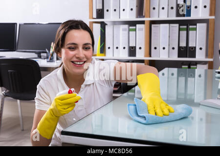 Close-up Of A Smiling Young Woman Cleaning The Glass Office Desk With Rag In Office - Stock Photo