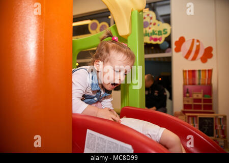 Happy little kid girl play in the playing room sliding off the slide. Funny child having fun indoors. - Stock Photo