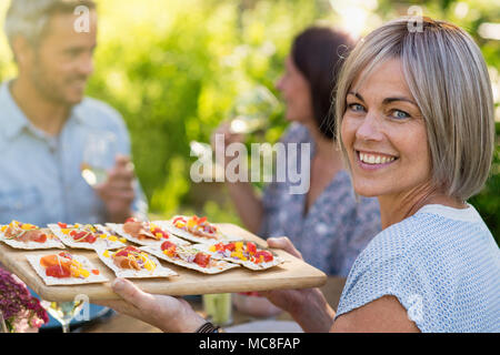 In summer. Group of friends gathered around a table in the garden to share a meal. a beautiful woman serves them snacks on a platter while looking at  - Stock Photo