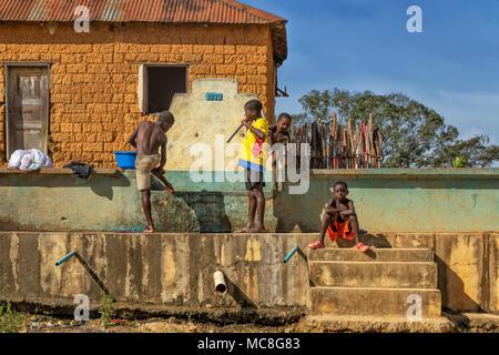 MALANJE/ANGOLA - 10 MAR 2018 - African boys playing in water fountain, rural area of Africa, Angola, Malanje. - Stock Photo