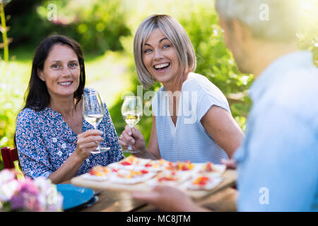 group of friends in their forties gathered around a table in the garden to share a meal. A man offers snacks to guests - Stock Photo