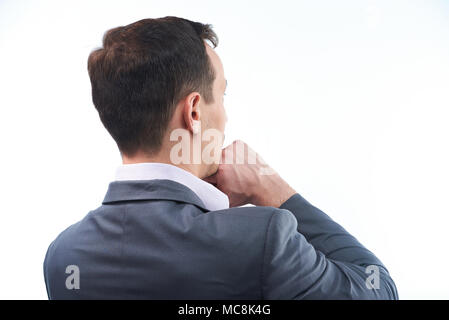 Back view of thinking man. Man with hand under chin - Stock Photo