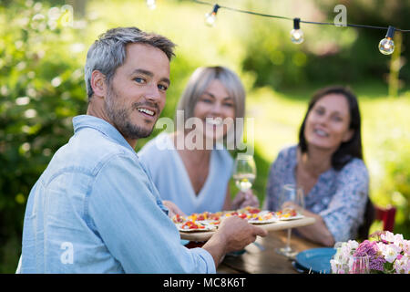group of friends in their forties gathered around a table in the garden to share a meal. A man offers snacks to guests while looking at the camera - Stock Photo