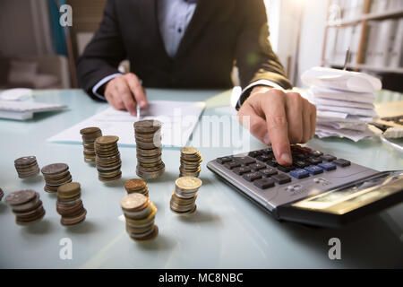 Close-up Of Stacked Coins In Front Of Businessman Working On Document - Stock Photo