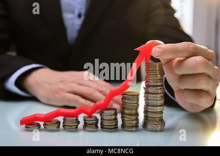Close-up Of A Businessperson's Hand Holding Red Arrow Over Increasing Stacked Coins - Stock Photo