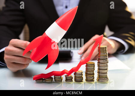 Businessperson's Hand Flying Red Rocket Over Stacked Coins And Arrow Showing Upward Direction - Stock Photo