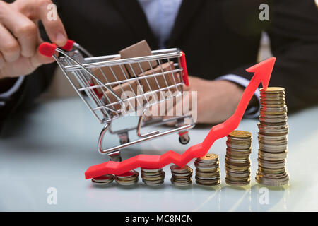 Stacked Coins And Arrow Showing Upward Direction In Front Of Businessperson Holding Shopping Cart - Stock Photo